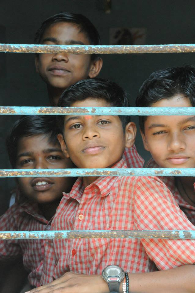 Indian+students+peek+through+the+windows+of+their+school
